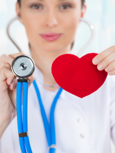 A female doctor is holding a paper heart that is red, and the end of a stethoscope . The instrument has blue sound pipes and chrome ear holders. The doctor is dressed in all white.