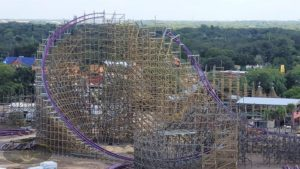 A wide shot of the entire Iron Gwazi Roller Coaster. There are trees in the background, and wooden trusses and purple track.