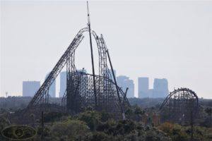 A crane lifts the top track. The background of the picture is the skyline of Tampa.