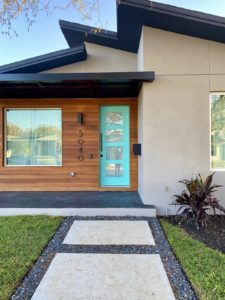 """Patti's House Has a """"Tiffany Blue"""" Front Door It is surrounded by a wood facade."""