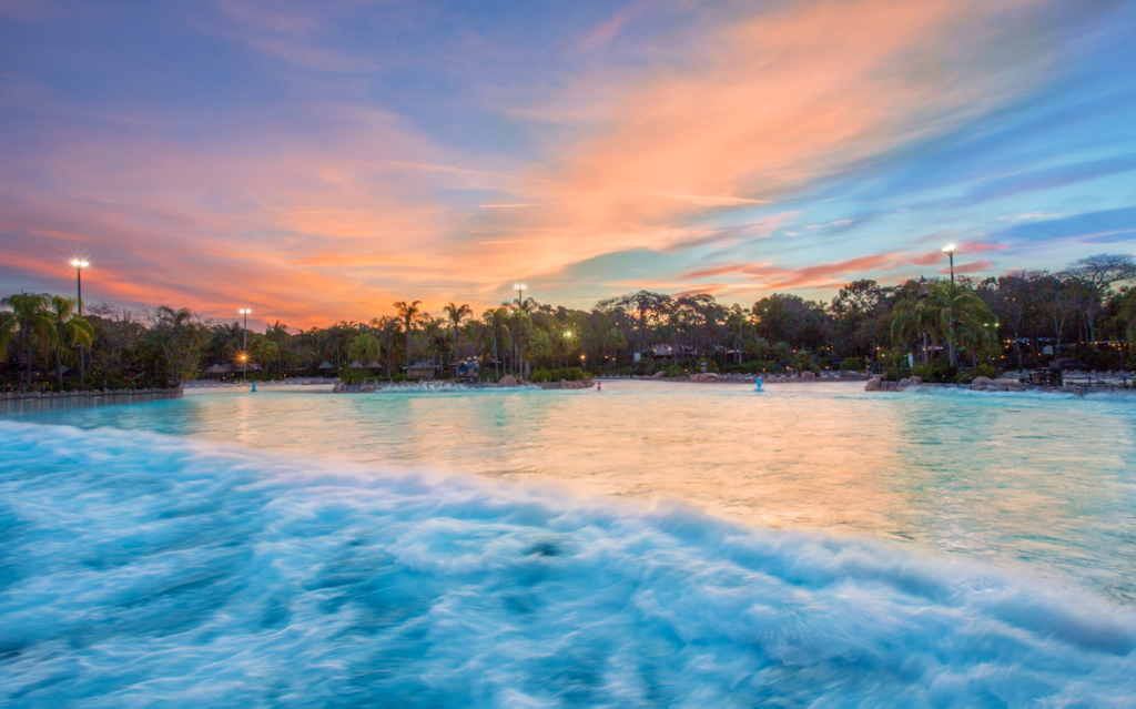 Wave Pool at Typhoon Lagoon. Also this picture is taken near sunset. The clouds are orange and pink and the water is teal blue.