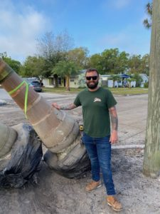 Also, Bryan Shows the Big Base of a Royal Palm He is About to Install. He has a full beard and wearing a green shirt and blue jeans.