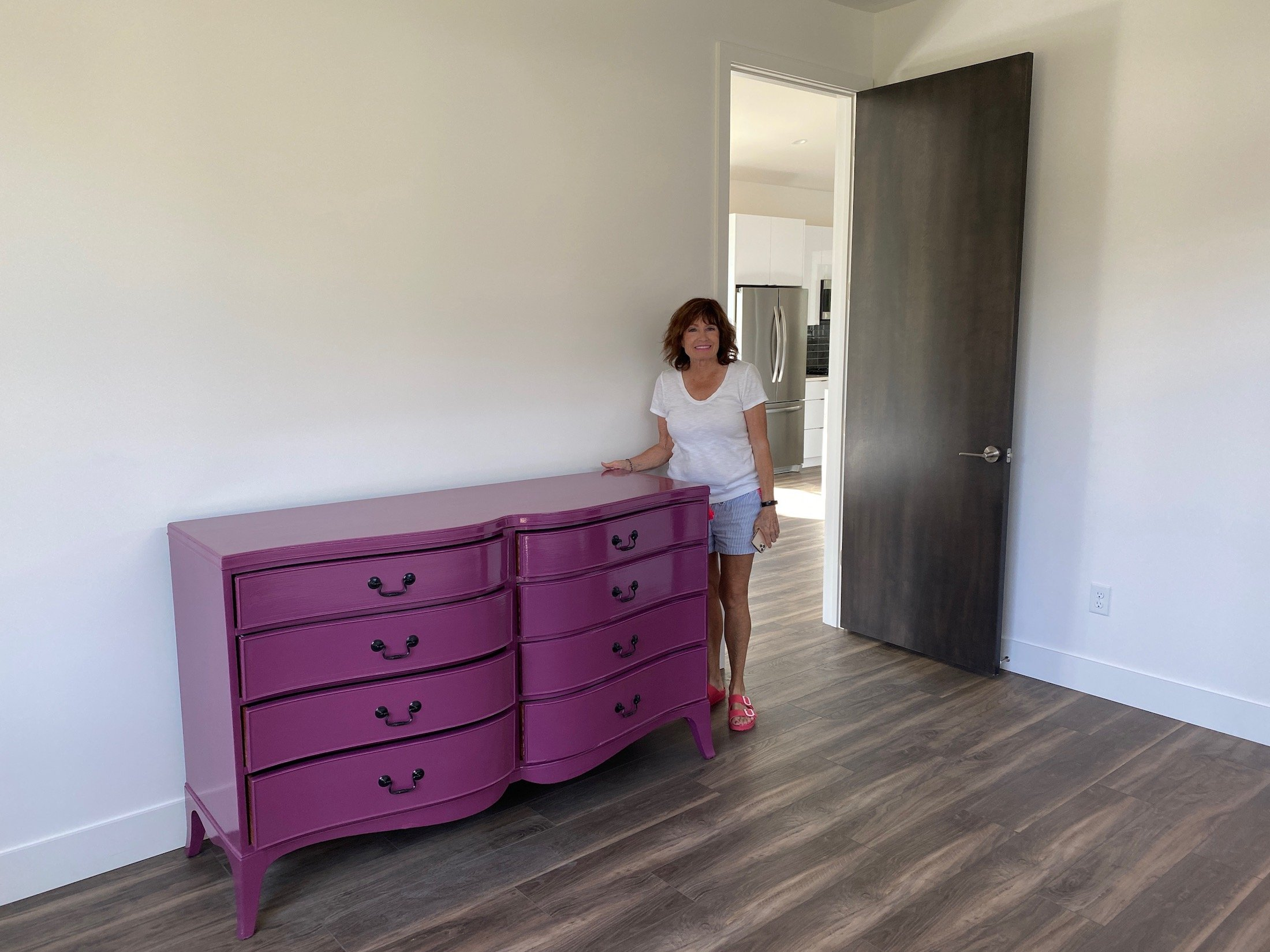 Moreover, the new mulberry colored dresser creates a happy room. Aunt Pam is standing beside it in the picture. Also, There are white walls and a black door.