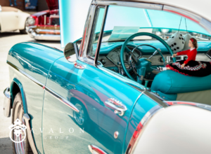 A photo of a classic car that is painted teal and white with chrome accents.