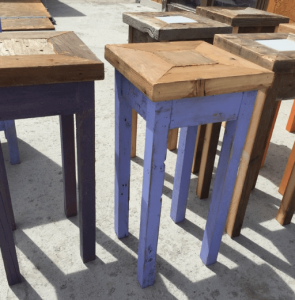 A group of tall square nightstands, one with legs painted purple
