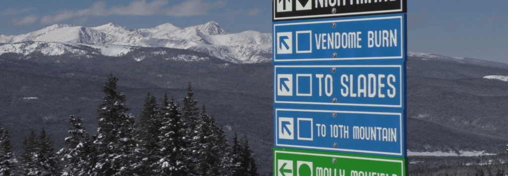 Photo of a sign indicating directions to various ski runs, with snowcapped mountains in the background