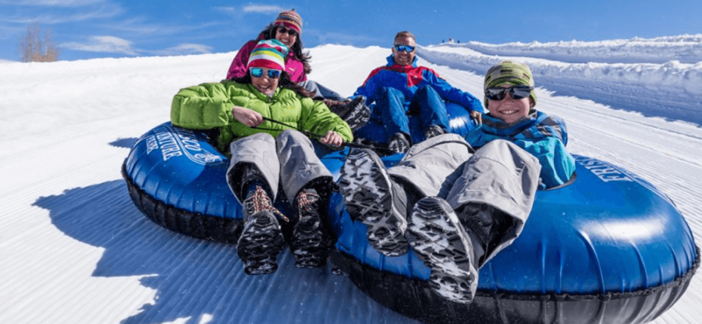 Photo of a family of four sitting on blue tubes in a groomed snow chute