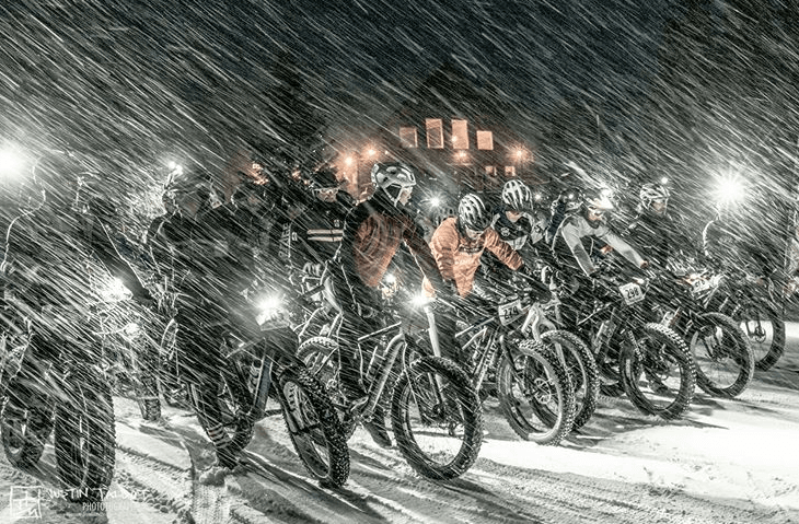 Fat tire bikers waiting for the race to start at night as snow pours down