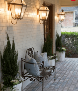 Exterior home photo showing a wall with sconces and a paver patio with a wrought-iron bench