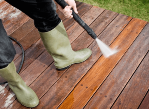 Downward looking view of a person wearing boots and holding a power washer, spraying a wooden deck