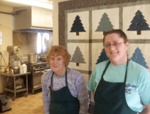 Two members of Senior Services standing in a kitchen and smiling