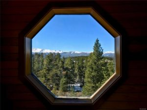 View of woods and mountains through a porthole window
