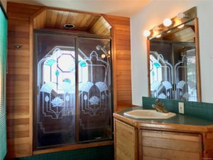 Green vanity and shower stall with etched glass design and wood paneling