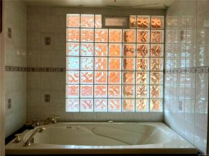 White jet bathtub in a corner with a tall wall of glass blocks