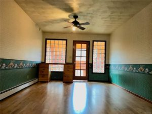 Room with wood floors, green wall paint, and glass block windows