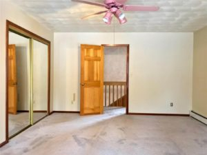 Carpeted room with pink ceiling fan and closet with sliding mirror doors