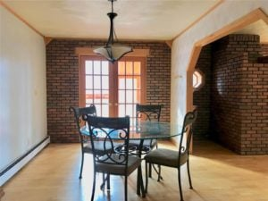 Small glass table and wrought iron chairs in a room with wood floors and brick wall