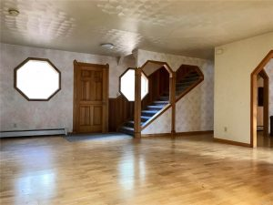 Expansive wood floor in open room with view of stairs leading up
