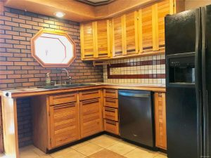 Custom wood cabinets in kitchen with porthole window and brick and tile details