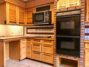 Vintage microwave and stove in kitchen with lots of custom wood cabinets