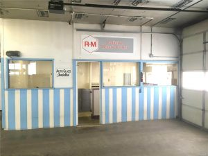 "Blue and white trimmed office inside garage; signs say ""RM Collision Repair Center"" and ""Auto Glass Installed"""