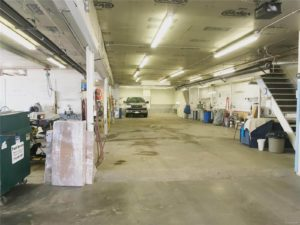 Long interior garage with concrete floors, fluorescent lighting, and equipment along the walls