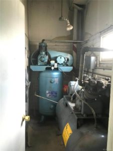 Small machine room with a generator and what appears to be a boiler