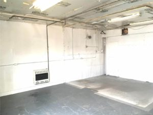 Interior of bare unfurnished room with lots of electrical conduit and some kind of heating unit on the wall