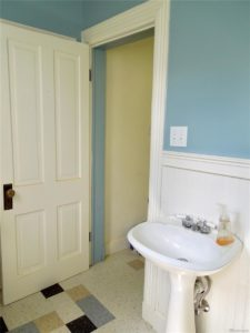 White sink and wainscoting in a bathroom with teal wall paint and a white door