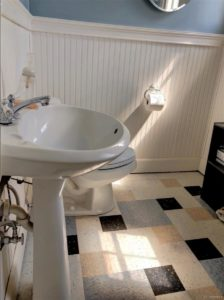 White, dark blue, light blue, and tan floortiles in a bathroom showing white commode and sink