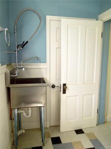 Industrial sink in a bathroom with teal wall paint and a white door