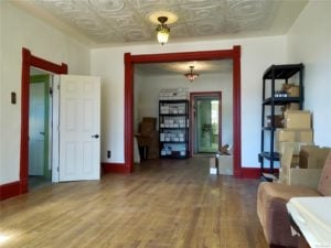 View from the front of the house looking back: hardwood floors, white pressed tin ceiling, red-trimmed doorframes