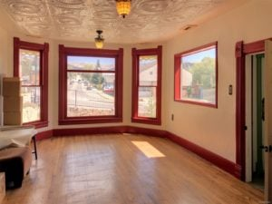 Front room with hardwood floors, white pressed tin ceiling, antique stained glass ceiling lamps, and views of the street through the bay window