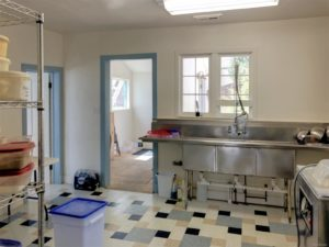 Kitchen area with big industrial sink and white, dark blue, light blue, and tan floortiles