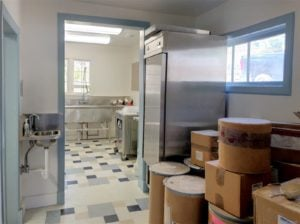 Looking into the kitchen: There's a pile of boxes and industrial fridge in the foreground; background has industrial sink and fluorescent lights