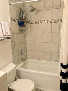 Bright white bathroom with commode and tub/shower