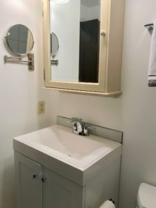 Square bathroom sink with cream-colored vanity and side pullout mirror on the wall