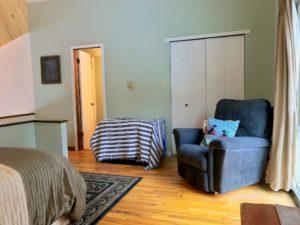 Bedroom with light green walls, black sofa chair, white closet doors, and open bathroom door
