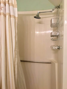 Shower with light-colored curtain, metal showerhead, and rung to hold onto