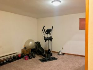 Carpeted room with stair-step machine and line of free weights