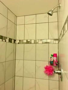 Inside of shower with white tiles that match the tiles in the main-floor bathroom