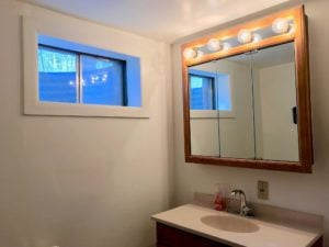 Oval bathroom sink with three-paneled cabinet that has round light bulbs above it