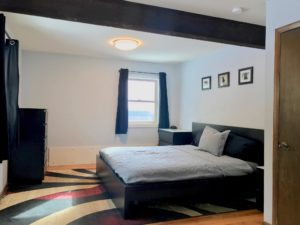 Black bed, dresser, and nightstands in a bedroom with white walls and exposed rafter