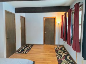 Bedroom with wood floors, three doors, and red curtains