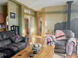 Bright living room with oversize sofa and chair, wood stove in background