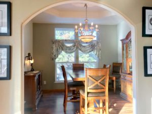 Arched entryway to a dining area with wooden table and chairs, hutch, and chandelier