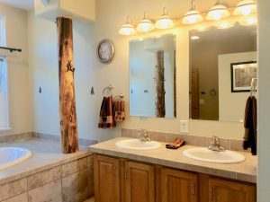 Bathroom vanity with double sink and mirrors, oval drop-in tub with wood pillar to the left
