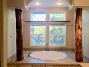 Oval drop-in tub set back into an alcove with two log pillars and a window behind