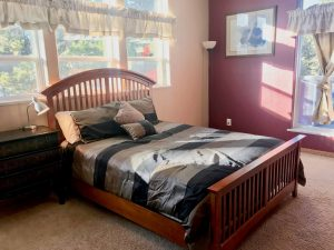 Full-size bed with headboard in a carpeted room with one wall painted burgundy and the other white, big windows letting in lots of light