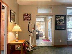 Room with dark green carpet, small table with lamp, stair-stepper exercise machine in the corner. There are 3 big pictures hanging on the wall, and you can see through the length of the house
